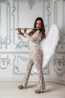 手と翼にフルートを持つステージ衣装ドレスの肖像画の若い女性モデル。フルート奏者の織り目加工の壁にある管楽器。広告学校のポスター。音楽またはコンサートのコンセプト作品