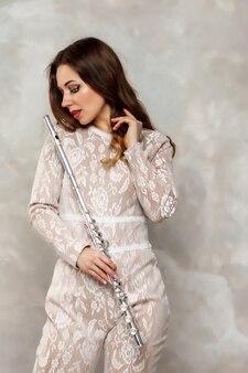 手にフルートを持つステージ衣装ドレスの肖像画の若い女性モデル。テクスチャード加工の壁の背景にフルート奏者の管楽器。広告学校のポスター。音楽またはコンサートのコンセプト作品