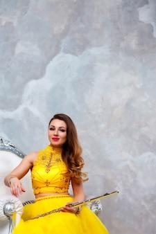 手にフルートとステージ黄色のドレスの肖像画の若い女性モデル。テクスチャード加工の壁の背景にフルート奏者の管楽器。広告学校のポスター。音楽またはコンサートのコンセプト作品