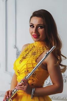 Модель молодой женщины портрета в платье этапа желтое с флейтой в руках. духовой инструмент у флейтиста на фоне текстурированной стены. плакат для рекламной школы. концептуальное произведение музыки или концерта