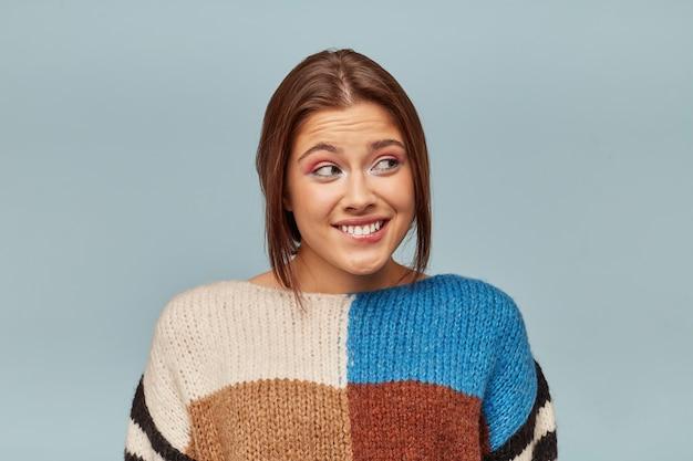 Ritratto di giovane donna in un maglione multicolore si sente in colpa guarda con ansia di lato, si è morsa il labbro