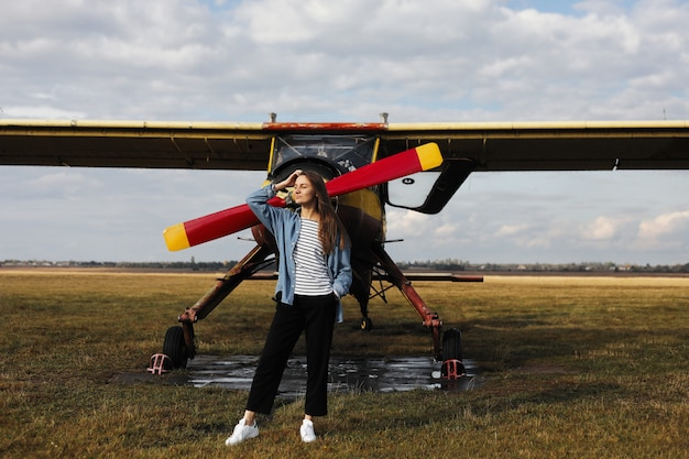 Portrait of young woman near the retro plane. field with plane flying over it.
