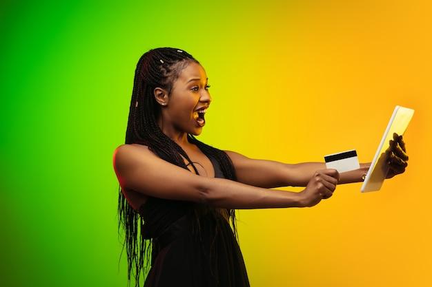 Ritratto di giovane donna in luce al neon su sfondo sfumato. ridendo e tenendo in mano un tablet e una carta di credito.