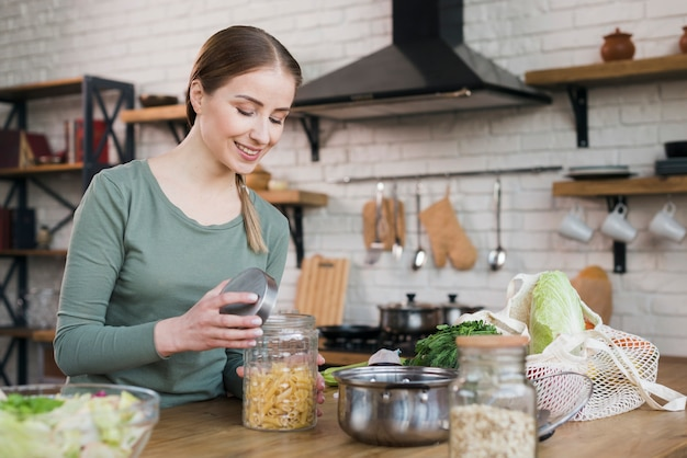 Portrait of young woman opening jar with organic pasta