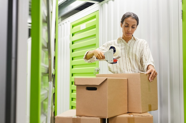 Portrait of young woman packing boxes with tape gun while standing by self storage unit, copy space