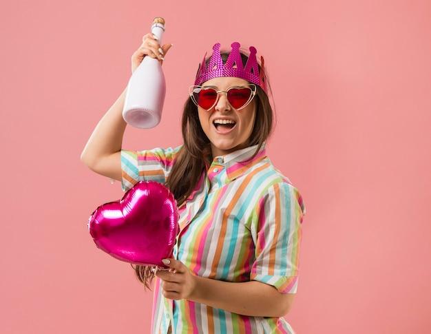 Ritratto di giovane donna alla festa con palloncino e bottiglia di champagne