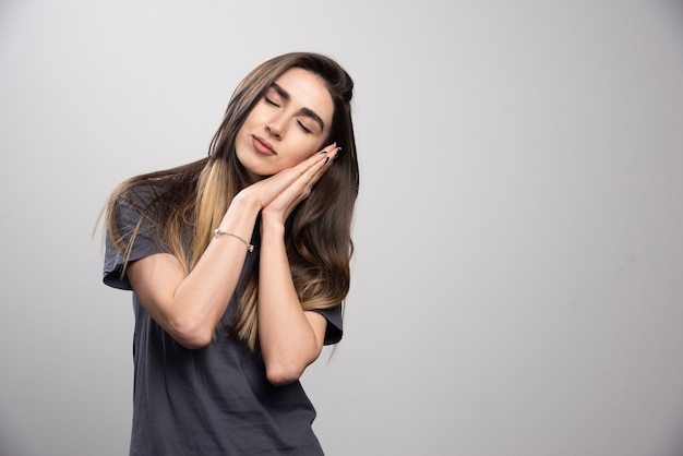 Portrait of a young woman peacefully sleeping shot on a gray background .