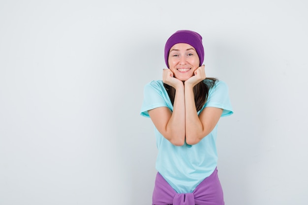 Portrait of young woman pillowing face on her hands in t-shirt, beanie and looking joyful front view