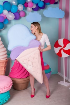 Portrait of young woman in pink dress holding big ice cream and posing on decorated background. amazing sweet-tooth girl surrounded by toy sweets.