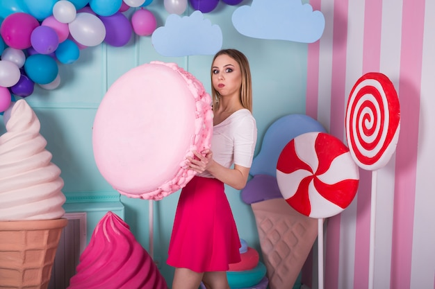 Portrait of young woman in pink dress holding big macaroon and posing. amazing sweet-tooth girl surrounded by toy sweets.