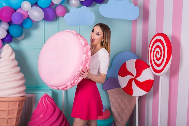 Portrait of young woman in pink dress holding big macaroon and posing on decorated background