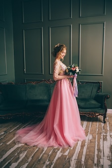 Portrait of a young woman in a pink dress holding a bouquet in her hands against a vintage interior background