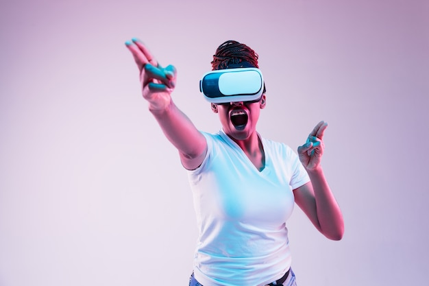 Portrait of young woman playing in vr-glasses in neon light