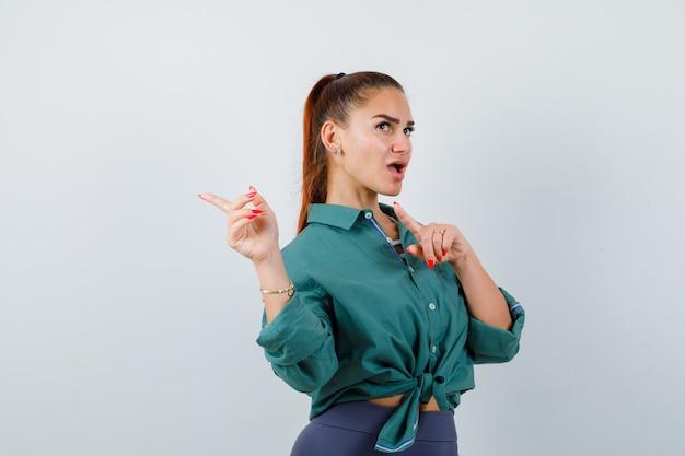 Ritratto di giovane donna che punta indietro con le dita indice, distogliendo lo sguardo in camicia verde e guardando la vista frontale pensierosa