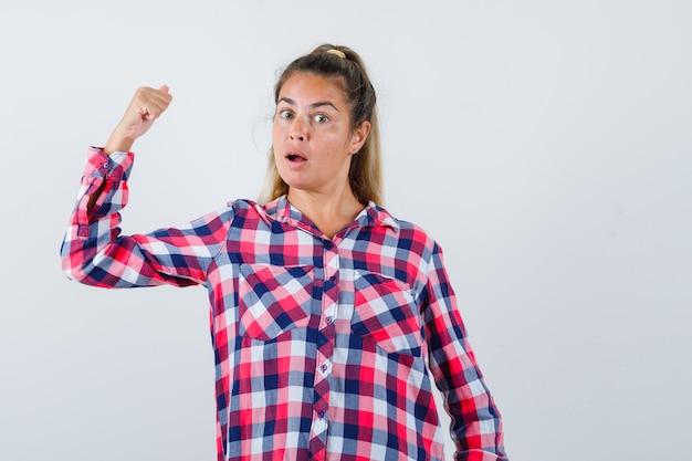 Ritratto di giovane donna che punta indietro con il pollice in camicia casual e guardando scioccato vista frontale