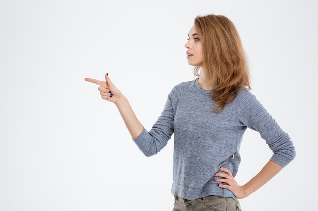 Portrait of a young woman pointing finger away isolated on a white background
