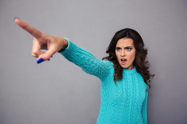 Portrait of a young woman pointing finger on something over gray wall