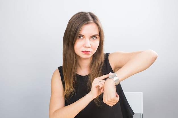 Portrait of a young woman pointing finger on wrist watch on a white background