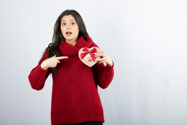 Ritratto di una giovane donna che indica a forma di cuore di una scatola regalo sul muro bianco.