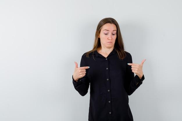 Ritratto di giovane donna che indica se stessa e sembra perplessa