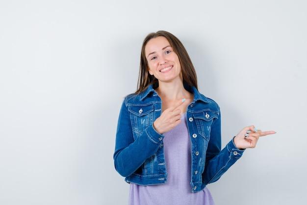 Ritratto di giovane donna che punta a destra in maglietta, giacca e sembra allegra vista frontale