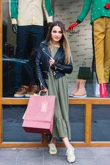 Portrait of a young woman posing in front of window display holding shopping bags in hand