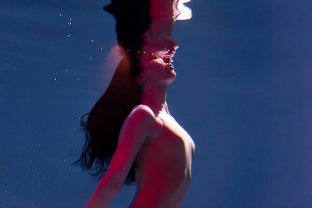 Portrait of young woman posing submerged underwater