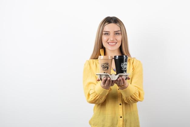 Ritratto di giovane donna in posa con tazze di caffè su sfondo bianco.
