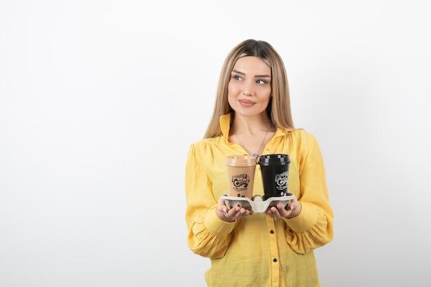 Ritratto di giovane donna in posa con tazze di caffè su bianco.