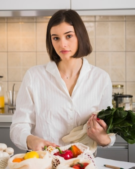 Portrait of young woman posing with organic vegetables