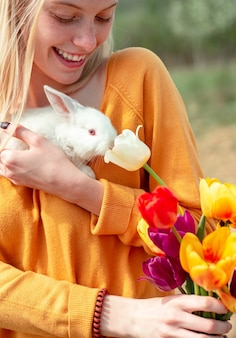 Portrait of young woman posing with rabbit lovely woman hold white rabbit