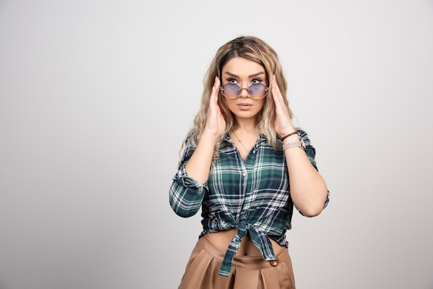 Portrait of young woman posing with stylish glasses.