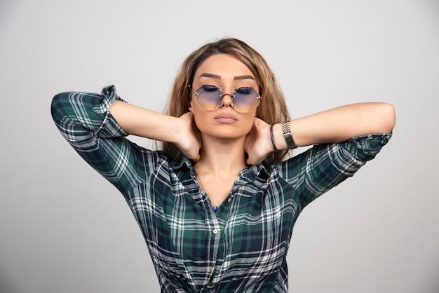 Ritratto di giovane donna in posa con occhiali alla moda.