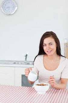 Portrait of a young woman pouring milk in her cereal