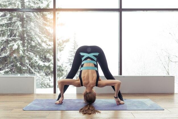 Portrait of young woman practicing yoga indoor near big window