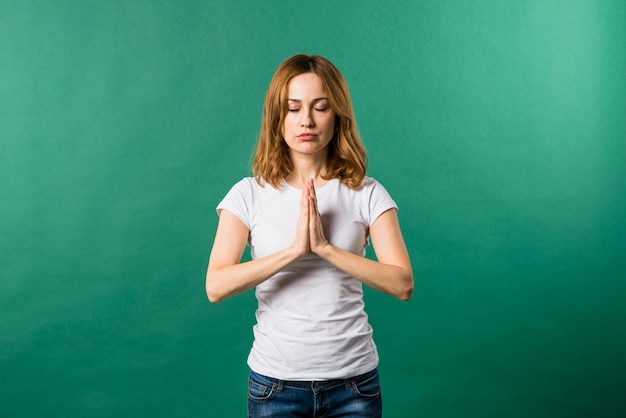 Portrait of a young woman praying against green background