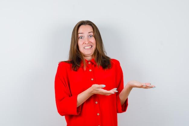 Ritratto di giovane donna che finge di mostrare qualcosa in camicetta rossa e sembra ansiosa vista frontale