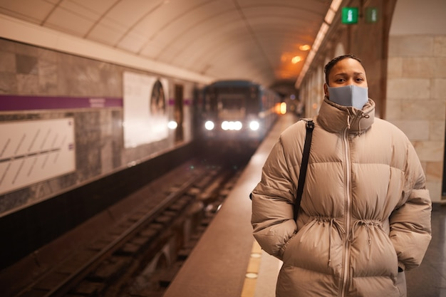 Portrait of young woman in protective mask looking at camera while standing in underground with train in the background