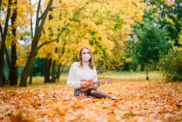 Portrait young woman in protective mask playing ukulele guitar in autumn park, lifestyle healthy travel concept