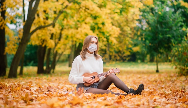 Portrait young woman in protective mask playing ukulele guitar in autumn park