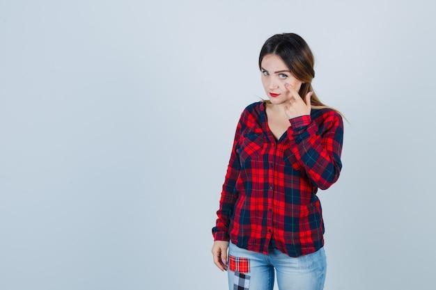 Ritratto di giovane donna che tira giù la palpebra in camicia a quadri, jeans e guarda fiduciosa vista frontale
