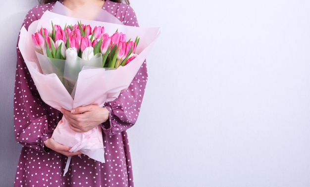 Portrait of a young woman in purple dress holding bouquet of pink and white tulips on grey .spring greeting card. .easter,spring flower concept.mothers or womans day.