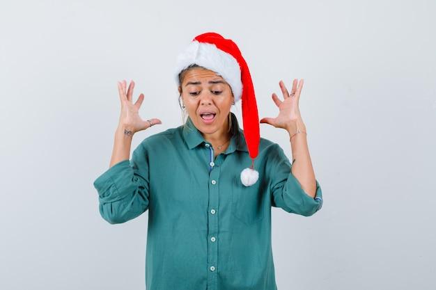 Ritratto di giovane donna che alza le mani mentre urla in camicia, cappello di babbo natale e guarda inorridita vista frontale