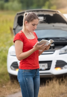 Portrait of young woman reading owner manual at broken car in meadow