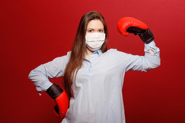 Portrait of young woman in red boxing gloves on red wall in protective medical mask
