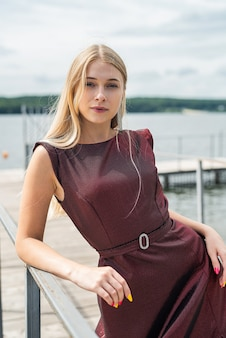 Portrait of young woman in a red dress near pond, relax and enjoy summer hot day, lifestyle