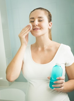 Portrait of young woman removing makeup with lotion and cotton pad