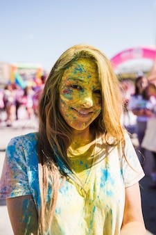 Portrait of a young woman's face covered with holi powder looking at camera
