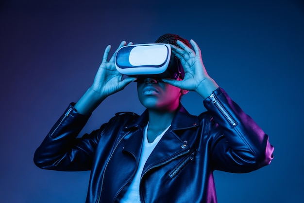 Portrait of young woman's playing in vr-glasses in neon light on blue