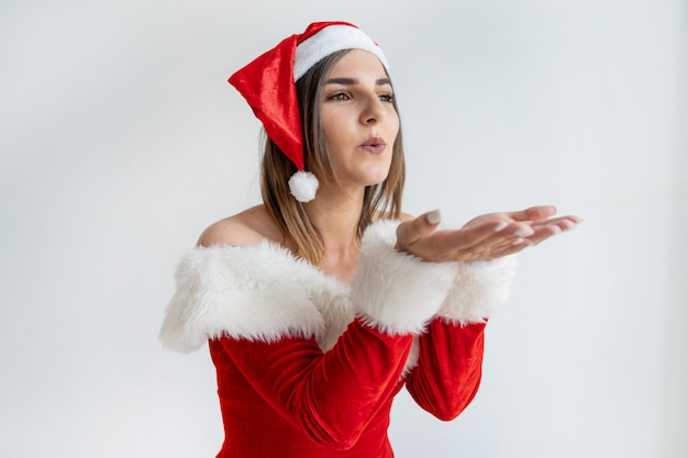 Portrait of young woman in santa claus outfit sending kiss